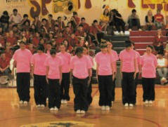 High School Breaker Girls dance group in neon pink T-shirts, in the gym