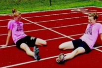 Shawnee Mission North High School track and field hurdlers wearing neon pink T-shirts during practice