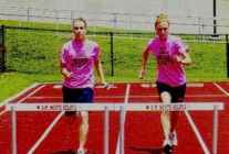 High School track and field hurdlers wearing neon pink T-shirts during practice, 2nd photo