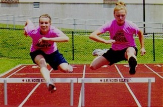 High School track and field hurdlers wearing neon pink T-shirts during practice, 3rd photo