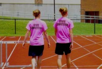 High School track and field hurdlers wearing neon pink T-shirts during practice, 5th photo
